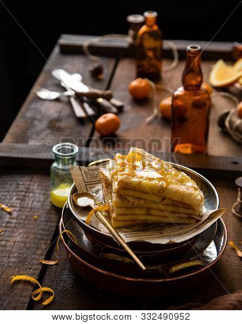 Homemade Stack Of Traditional French Thin Crepes Suzette With Orange Sauce In Copper Plates On Rusti