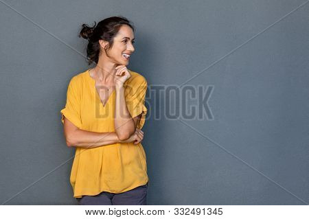 Mature beautiful latin woman isolated on grey background looking on side with copy space. Portrait of positive latin woman smiling. Happy middle aged lady standing against grey wall and thinking.