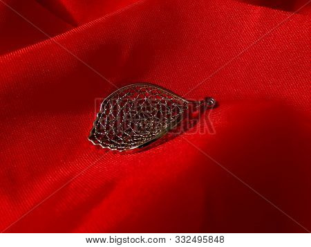 Jewelry On Red Silk Fabric. Beautiful Female Pendant Made Of 925 Sterling Silver. Necklace In The Fo