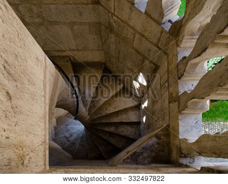 Top View Of A Spiral Staircase Made Of Stone. Between The Balusters A Green Lawn Is Visible. Below Y