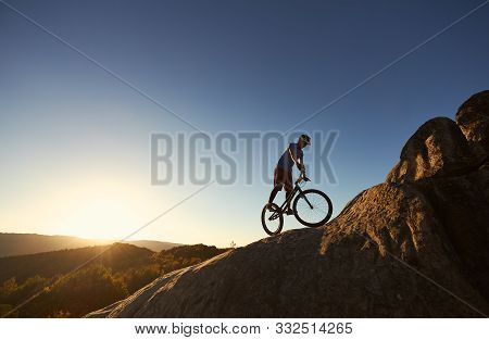 Silhouette of professional bicyclist balancing on trial bicycle on top of big boulder, male rider making acrobatic stunt on summer evening, blue sky and sunset on background. Concept of extreme sport poster