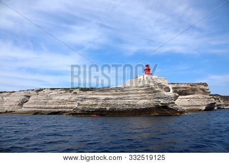 Small Red Lighthouse Near Bonifacio City In Corsica France And The Cliffed Coast