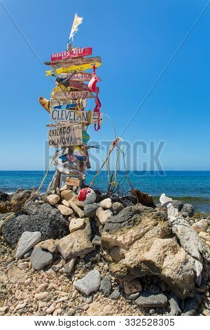 Signpost With Stones At Beach With Blue Ocean On Island Bonaire