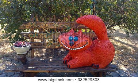 Russia, Novorossiysk, September 2015. Cheshire cat. Park Frunze. Character from the book Alice in Wonderland. Cheerful ginger cat on a bench. Blinding smile. The bench is decorated with decorative ornament, next to a flower bed with flowers. A cute pet se