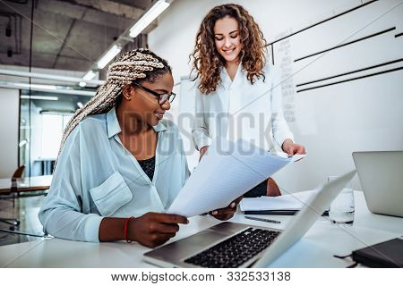 Two Young Women Work Together In A Bright Office. Work On The Project, Consultation.