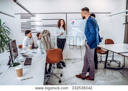 Young Business People Work In A Spacious Beautiful Office Together. A Young Business Woman Tells Her
