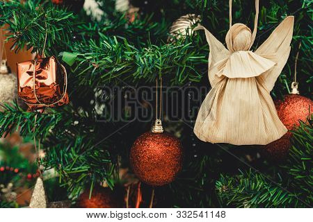 Corn Husk Doll On Christmas Tree. Red And Silver Christmas Balls, Baubles. Figure Made From Corn Hus