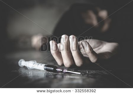 Woman Hand Of A Drug Addict And A Syringe With Narcotic Syringe Lying On The Floor, Overdose, Drug C