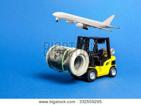 Forklift Truck Carries A Bundle Of Dollars And Airplane. Export Of Capital, Offshore Economic Zones.