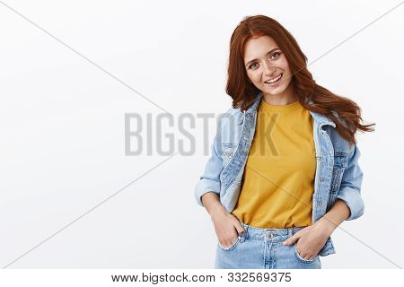 Stylish Good-looking European Girl With Red Curly Hairstyle In Denim Jacket, Hold Hands In Pockets,