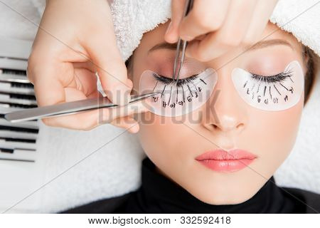 Eyelash Extension Procedure. Master Tweezers Fake Long Lashes Beautiful Female Eyes