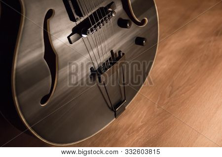 Black Jazz Archtop Guitar With Holes. Hollow Steel-stringed Acoustic Or Semiacoustic