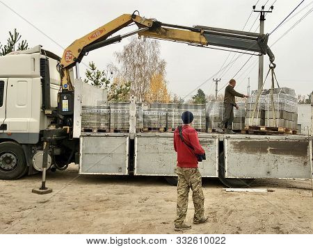 Unloading Paving Slabs From A Truck. Men Unload Paving Slabs Using A Manipulator. Workers Take Build