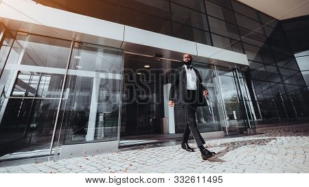 An Elegant Bearded Bald African Man Entrepreneur Is Leaving A Business Skyscraper, He Has Just Passe