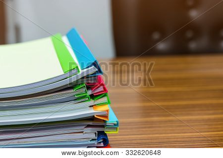 Pile Of Unfinished Paperwork Stacked In Archive With Plastic Slide Binder Bars On Office Table Waiti