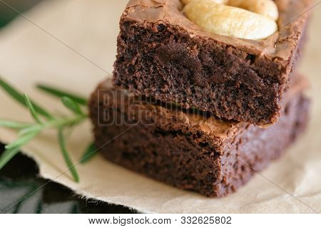 Fresh Baked Dark Chocolate Fudge Brownies. Sweet Brownie Topping With Cashew Nut Stacked On Brown Pa