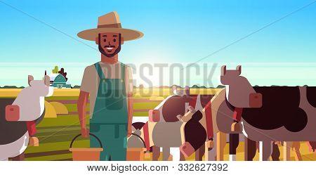 Milkman Holding Buckets With Fresh Milk Farmer Standing Near Herd Of Cows Grazing On Grassy Field Ec