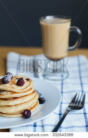 Small Circular Slapjack Or Oladyi With Blackberry, Frozen Berries On Plate, Fork And Coffee On Table