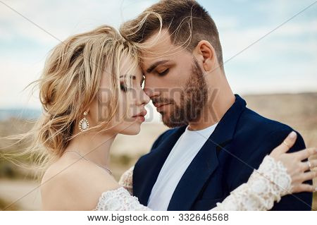 Love Story Of A Woman And A Man. Loving Couple Embraces, A Beautiful Oriental Couple. A Man In A Jac