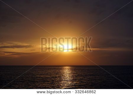 Wonderful Sunset On The Sea. The Sun Goes Down To The Horizon In Small Clouds. A Wonderful Evening O