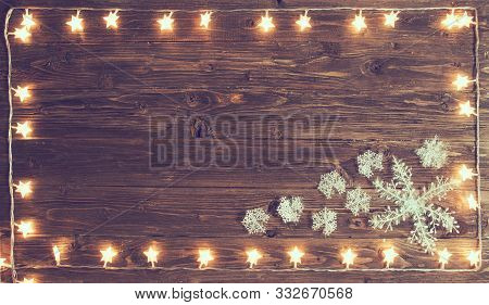 Christmas Warm Gold Garland Lights With Snowflakes On Wooden Rustic Background. Christmas Or New Yea