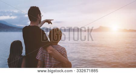 Father With Son And Daughter Near River At Sunset. Dad And Kids Watching Sunrise Together. Happy Man