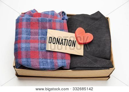 Donation Concept. Donation Box With Donation Clothes On A White Background. Charity. Helping Needy P