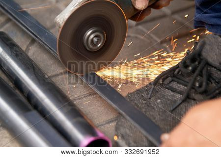 The Worker Is Sawing And Cutting Metal Part Of Steel In A Shop.