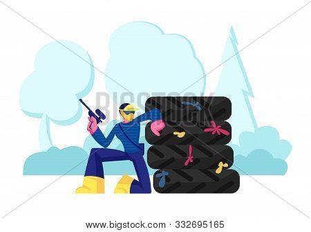 Extreme Paintball Battle. Player In Protective Uniform, Mask And Gun Hiding Behind Of Tires Embrasur