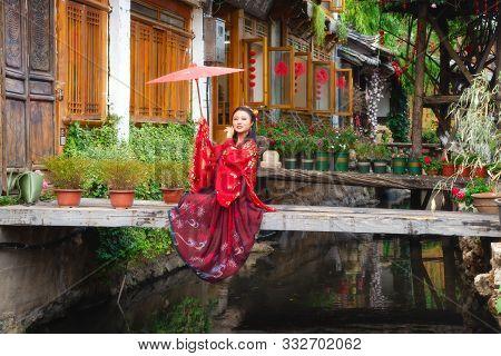 Lijiang, China - April 29, 2019: A Fashion Model With Traditonal Clothing And Umbrella Posing In Lij