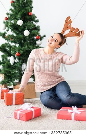 Christmas, X-mas, Winter, Happiness Concept - Girl Opens A Gift Against The Background Of The Christ