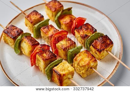 Paneer Tikka At Skewers In White Plate Isolated At White Background. Paneer Tikka Is An Indian Cuisi