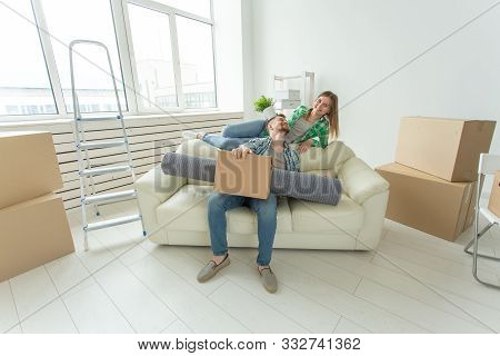 Cheerful Young Couple Rejoices In Moving To A New Home Laying Out Their Belongings In The Living Roo