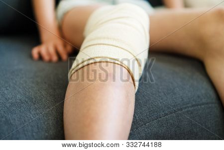 Child Knee With Gauze Bandage. Close-up View.