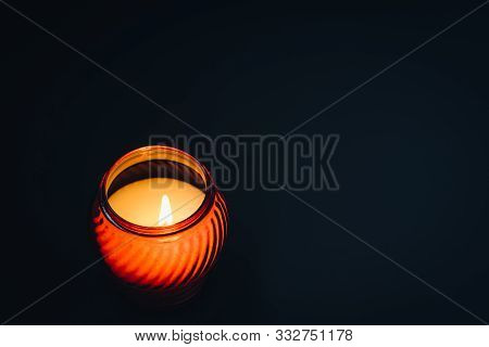 White Burning Candle In Red Glass On A Black Background.. Mourning, Burning Candle. White Burning Ca