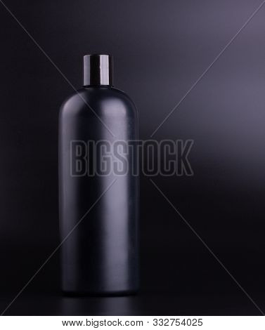 Big Black Hair Shampoo Bottle On Black Background