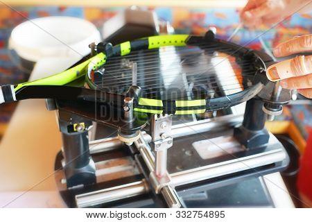 Stringer Pulls Strings On Tennis Racket On Equipment Stringing Machine.