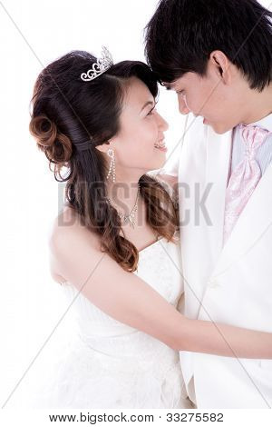 Portrait of young elegant enamoured just married groom and bride embracing at Wedding on isolated white background