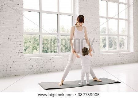 Young Mother Does Physical Yoga Exercises Together With Her Baby, Mother And Little Child Holding Ha