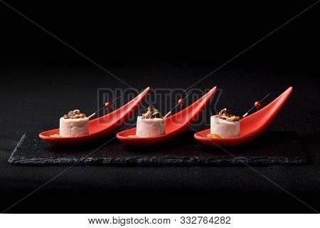 Goose liver pate, foie gras, served on black stone in Japanese red spoons. Paste served with jam and nuts. Fusion food concept, low key, copy space. poster