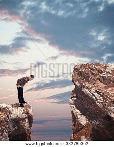 Kid Looking Down Over A Gap Between Two Mountain Peaks.
