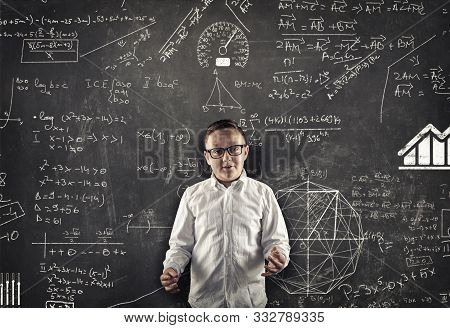 Student Explaining Math Formulas In Classroom , In Front Of The Blackboard Full Of Math Formulas.