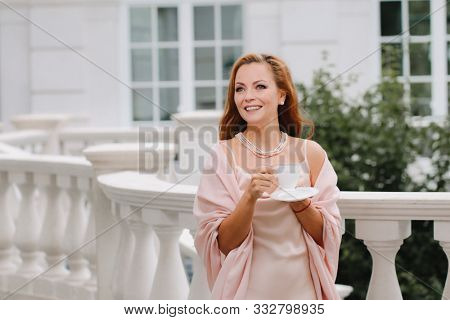 Beautiful lady in luxurious ballroom dress drinking coffee against Baluster railing of her palace. Vintage concept