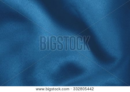 Dark Blue Colored Background Of Soft Draped Fabric. Beautiful Satin Silk Textured Cloth For Making C