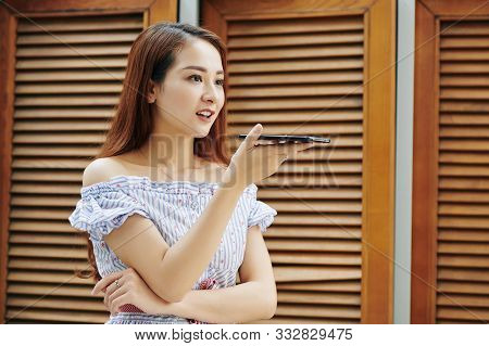 Portrait Of Young Attactive Vietnamese Woman Recording Voice Message For Her Friend