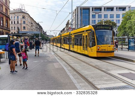 BUDAPEST, HUNGARY - AUGUST 12, 2019: People waiting for the tram on line 4 and 6 in the station Blaha Lujza ter. An important tram line in the public transport network of Budapest.