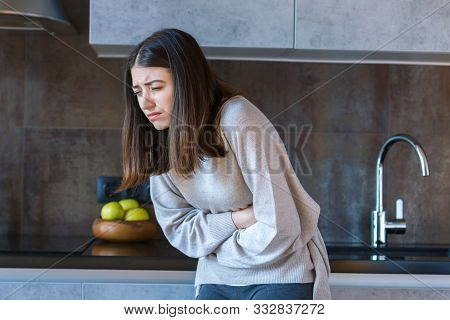 Young Woman In Grey Clothes Is Holding Hands On Belly. Brunette Girl Is Feeling Bad And Sick. Sudden