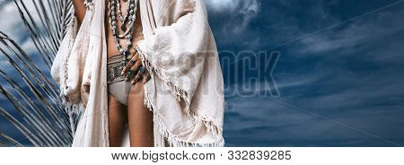 Close Up Of Young Fashionable Stylish Woman With Tanned Skin Wearing Stylish Boho Accessories On Blu