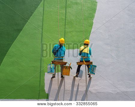 Two Painters Are Painting The Exterior Of The Building On A Dangerous Looking Scaffolding Hanging Fr