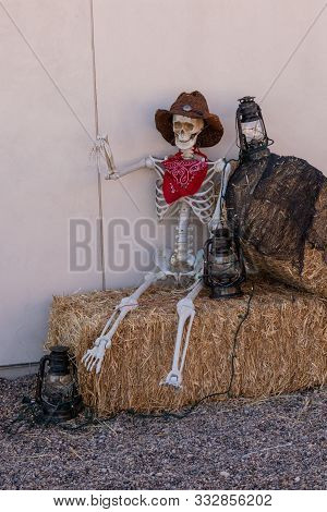 Skeleton Sitting On Hay Bales And Dressed In Hat And Neckerchief